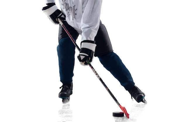 アイスコートと白い背景の上の棒を持つ認識できない男性のホッケー選手