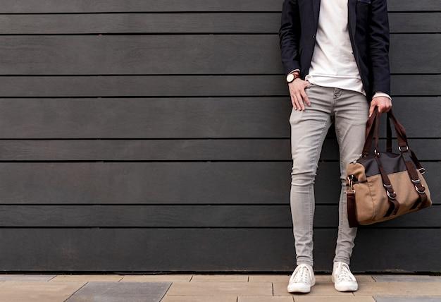 도시 거리에 현대적인 건물의 벽에 기대어 가방을 들고 주머니에 손을 잡고 세련된 캐주얼 복장을 입은 인식 할 수없는 남성