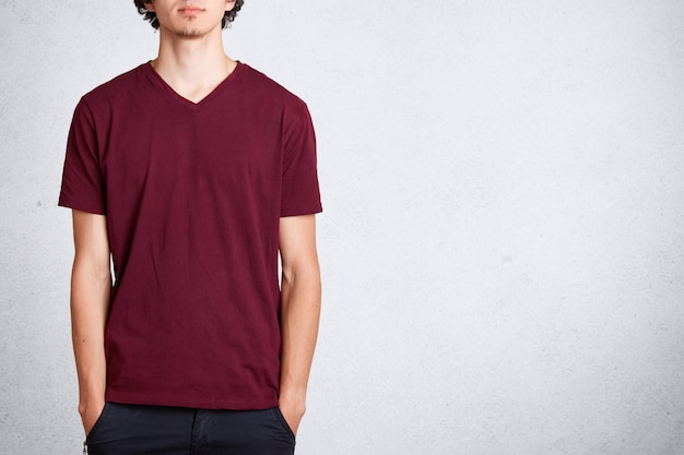 Unrecognizable male keeps hands in pocket, wears casual t shirt with blank copy space for your design or advertisement, stands on white. people and clothing concept