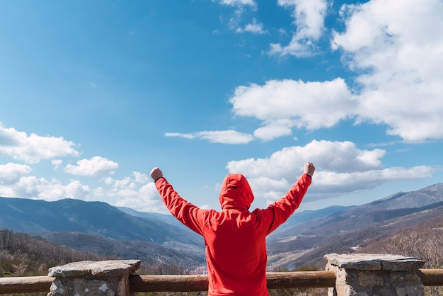 Неузнаваемый мужчина смотрит в небо с горами на заднем плане концепция свободы