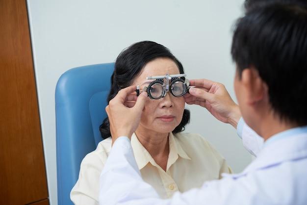 Неопознаваемый мужской офтальмолог, устанавливающий рамку пробной линзы для старшей пациентки