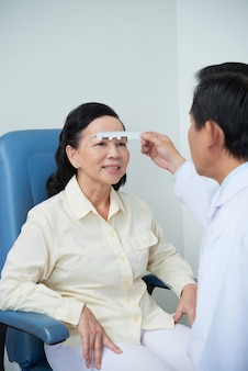 Unrecognizable male ophtalmologist performing eyesight check for asian female patient