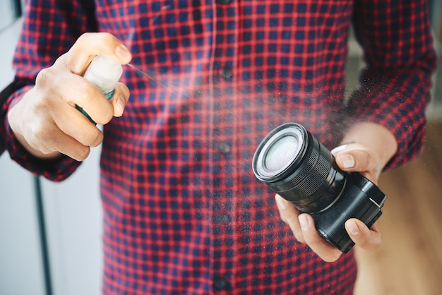 Unrecognizable male photographer spraying camera lens with cleaning fluid