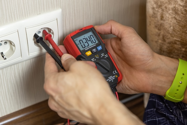 An unrecognizable male technician measures the voltage at the outlet with a digital multimeter. there are only hands in the frame, close-up. renovation concept, electrician in the apartment.