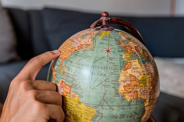 Unrecognizable male tourist picking country on retro world globe while planning travel