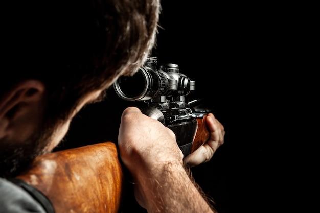 До неузнаваемости мужчина целится из охотничьего ружья в темноте