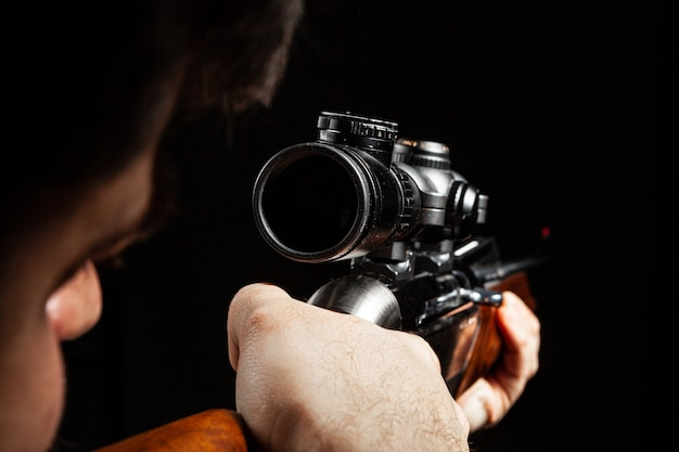 Unrecognizable man aiming with a hunting rifle in dark close up