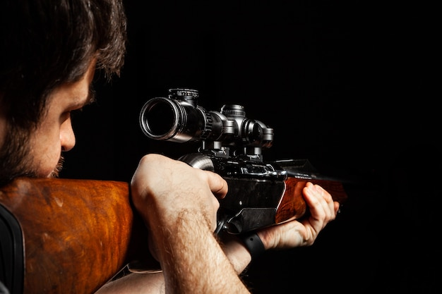 Unrecognizable man aiming with a hunting rifle in dark