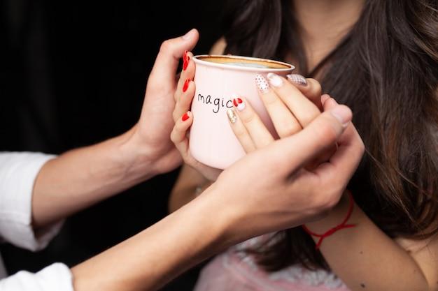 認識できない男と女が両手でホットコーヒーのマグカップを保持します。