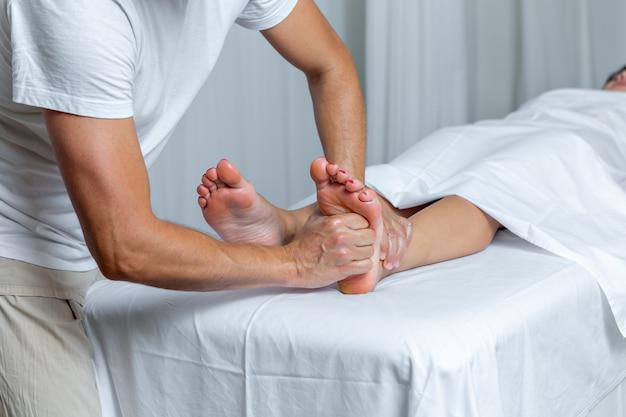 스파에서 반사 요법 마사지를 받는 여성의 발에 압력을 가하는 알아볼 수 없는 남자. 스파 개념입니다.