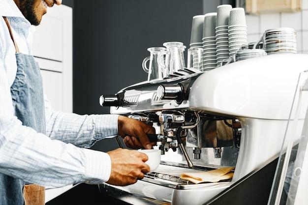 До неузнаваемости мужчина-бариста готовит кофе на профессиональной кофемашине крупным планом
