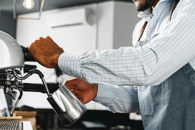 プロのコーヒーマシンでコーヒーを準備している認識できない男のバリスタがクローズアップ