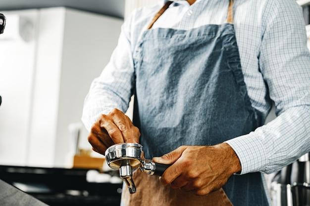 До неузнаваемости мужчина-бариста готовит кофе на профессиональной кофемашине