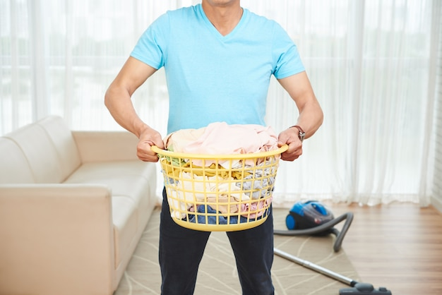 Unrecognizable man carryingfull laundry basket at home, and vacuum cleaner on floor
