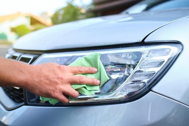 야외에서 걸레로 자동차 헤드라이트를 청소하는 알아볼 수 없는 남자