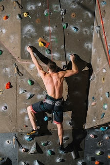 Unrecognizable man climbing wall