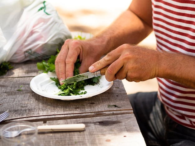 Unrecognizable man cutting parsley on plate on sunny day