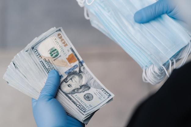 認識できない男は医療用マスクを販売した後、多くのお金を稼いだ、保護手袋を着用しています。コロナウイルスの発生と予防。流行中のフェイスマスクの不足。大きな予算。投機