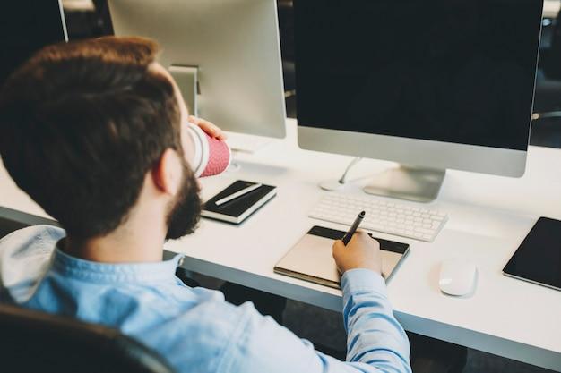 新鮮な温かい飲み物を楽しんでいて、オフィスで働いている間、空白の画面でモニターの近くにグラフィックタブレットで描く認識できない男