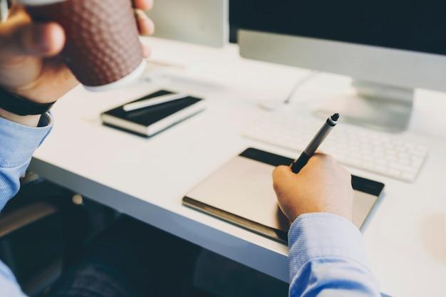 オフィスの机に座って熱い飲み物を楽しんでグラフィックタブレットに描く認識できない男。グラフィックタブレットを飲んで使用する作物デザイナー