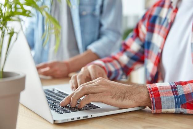 認識できない男性のフリーランサーとラップトップコンピューター上の彼のパートナーのキーボードは、遠くで動作します