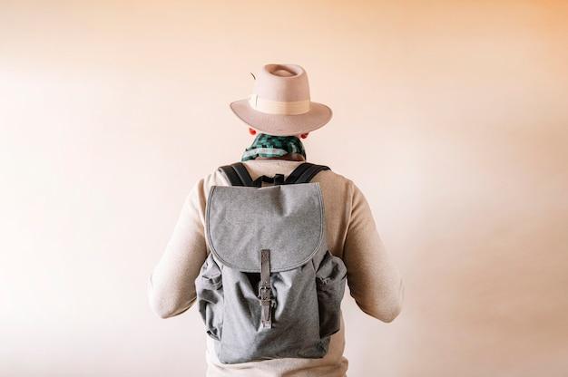 До неузнаваемости мужчина сзади в шляпе и рюкзаке.