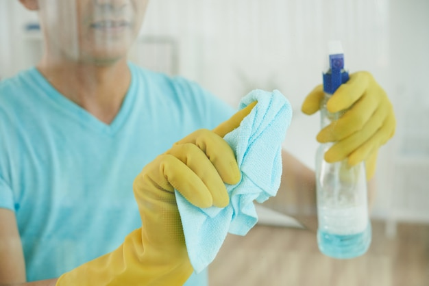 Unrecognizable man in gloves spraying window with cleaning liquid and wiping with cloth