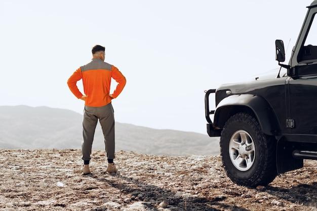 알 수없는 남자 등산객이 산 정상에 올라 계곡을 내려다보고 있습니다.