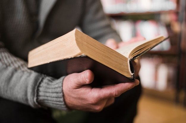 Unrecognizable man holding book close up