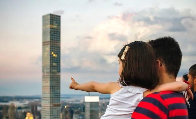 До неузнаваемости мужчина держит маленькую девочку, указывая небоскреб на горизонте манхэттена, в нью-йорке