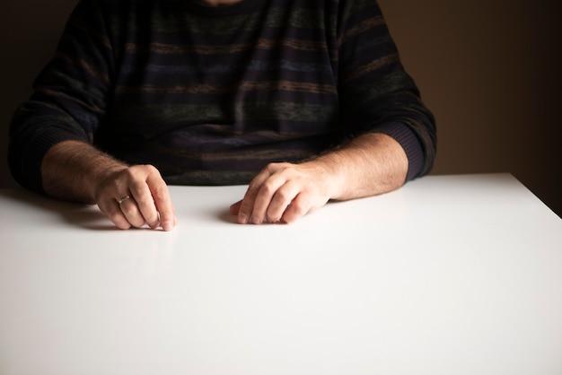 白い空のテーブルに座っている見慣れた位置にある認識できない男