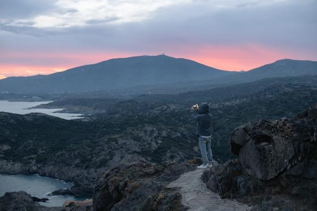 Неузнаваемый мужчина в толстовке с капюшоном стоит на вершине пешеходной тропы на горе