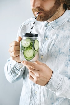 Unrecognizable man in light jeans shirt drinks fresh home made cucumber with mint sparkling lemonade through striped drinking straw from rustic transparent jar in hands