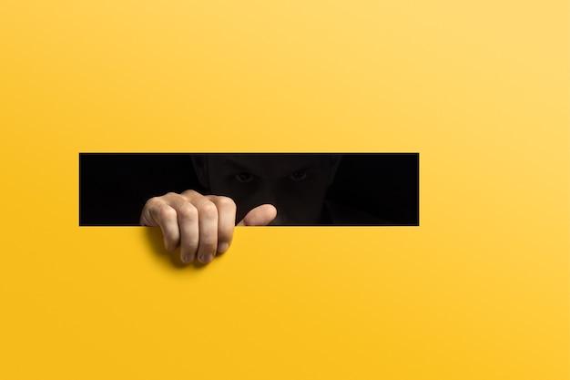 Неузнаваемый мужчина смотрит из темноты через щель. сосредоточьтесь на руке.
