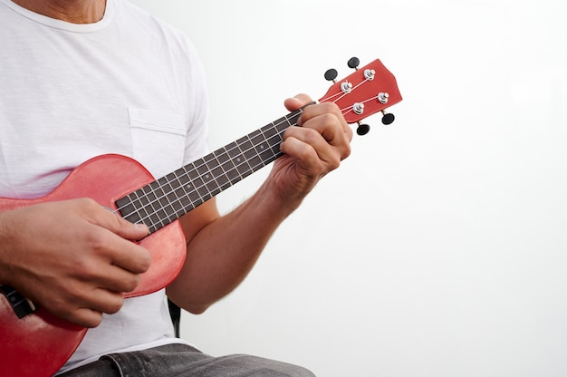 Unrecognizable man playing a red ukulele