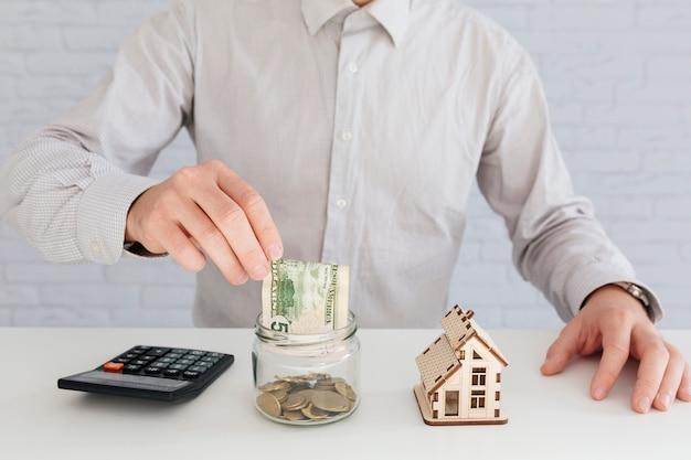 Unrecognizable man putting money to jar