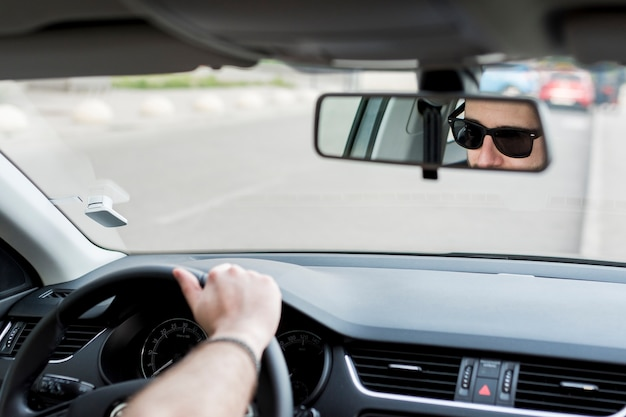 Unrecognizable man riding in car on busy road