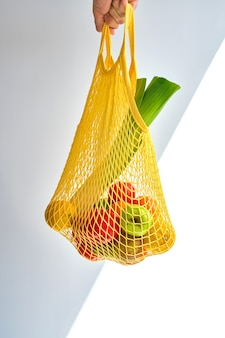 Unrecognizable man's hand holding a yellow bag of mixed fruit and vegetables