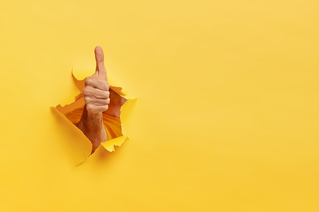 Unrecognizable man shows like gesture through torn yellow wall, keeps thumb up