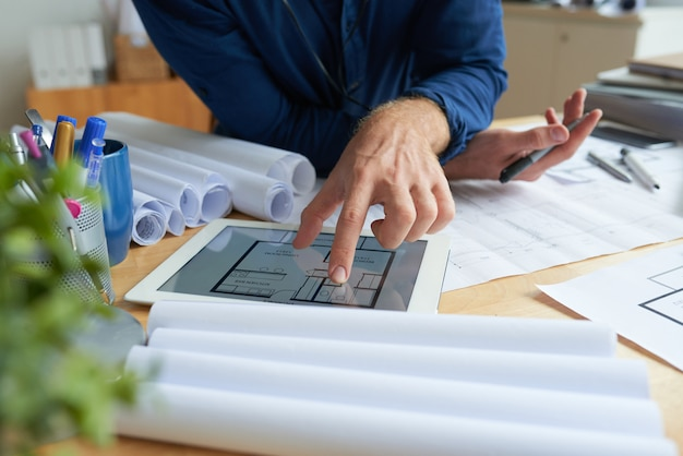 Unrecognizable man sitting at desk with technical drawings and looking at floor plan on tablet