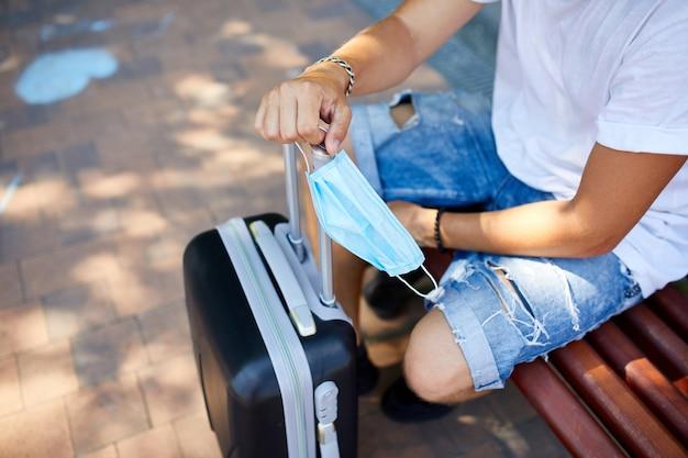 ベンチに座っている認識できない男とスーツケースと携帯電話を持って屋外の公園で彼の手に保護マスク、コロナウイルスパンデミック中の生活、空の旅、旅行のコンセプト。