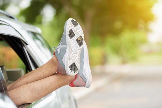 Unrecognizable man sticking out feet in trainers through car window
