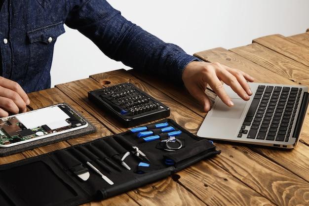 認識できない男は、ノートパソコンを使用して、電子機器を修理する方法のガイドを見つけるツールバッグと壊れたガジェットをヴィンテージの木製テーブルの近くに