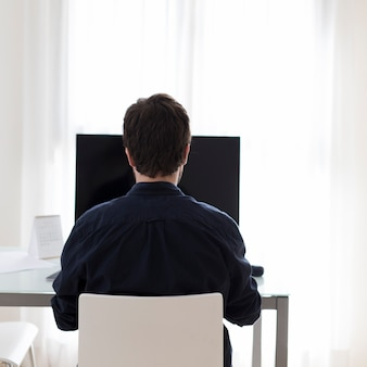 Unrecognizable man using computer in office