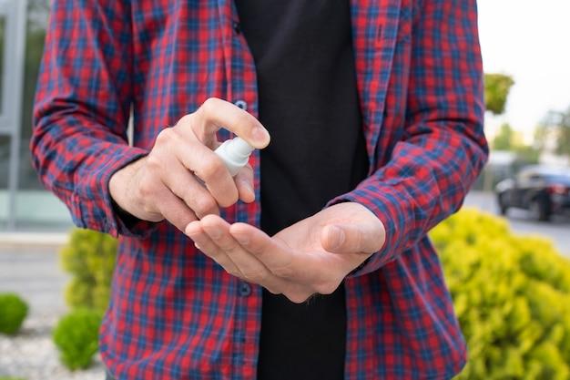Неузнаваемый мужчина с помощью дезинфицирующего средства на руках