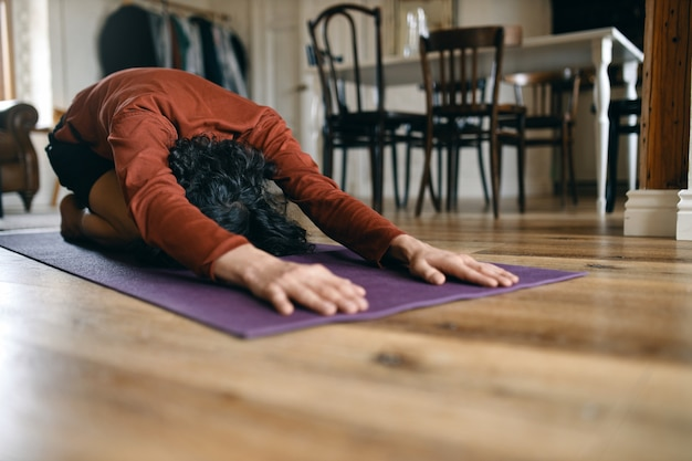 집에서 요가를하고, 발라 사나 또는 아이 포즈에서 휴식을 취하고, 아사나 사이의 신체 근육을 이완시키고, 허리와 엉덩이를 스트레칭하는 검은 머리를 가진 인식 할 수없는 남자. 휴식과 건강 개념