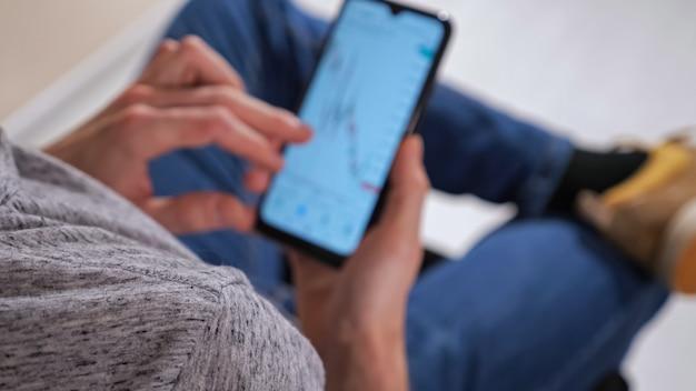До неузнаваемости мужчина с телефоном изучает анализ графиков фондового рынка.