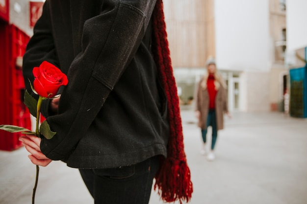 Unrecognizable man with red rose waiting for woman