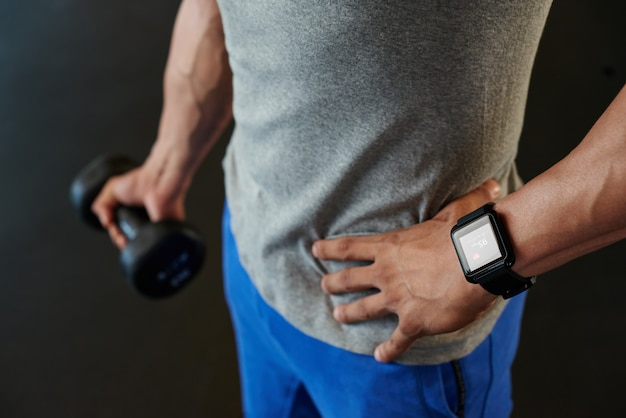 Unrecognizable man with smart watch holding dumbbell