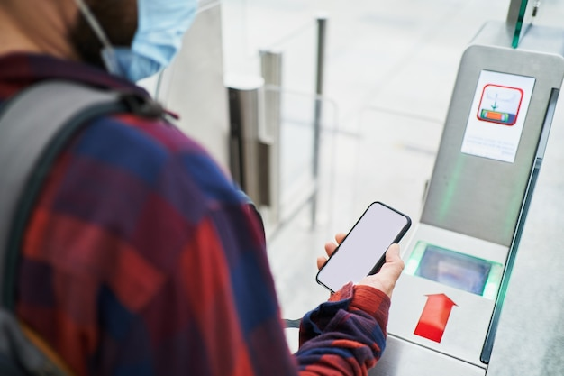 수술용 마스크를 쓴 알아볼 수 없는 남자가 공항 보안 스캔에서 qr 코드를 통과합니다.